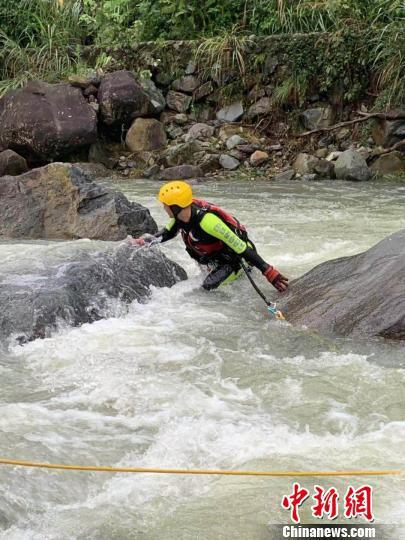 救援队员在湍急的水流中打捞遗体。 钟新 摄