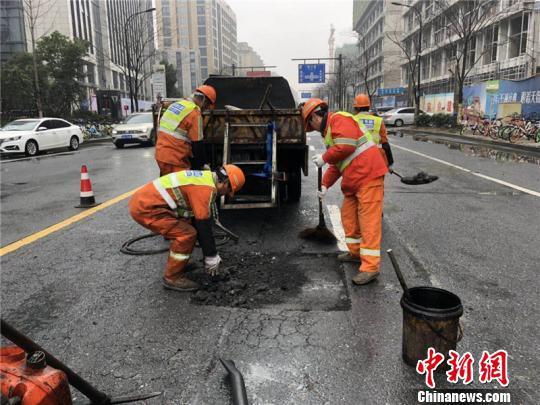 环卫工人修补雨天侵蚀的沥青路面。 西湖区城管局提供 摄