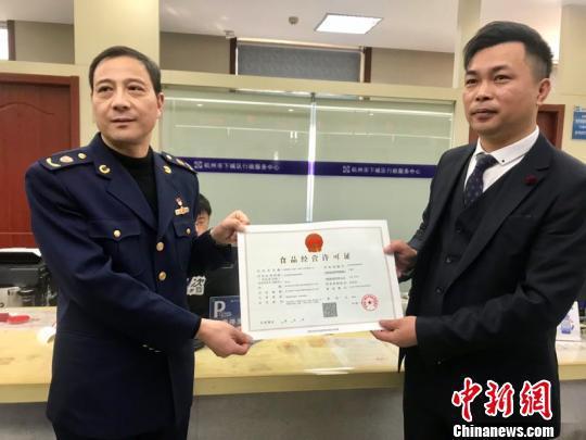 """杭州试点直营连锁餐饮经营企业""""评审承诺制""""颁发的首张证件。 刘方齐 摄"""