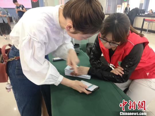 市民向志愿者咨询如何使用电子社保卡。 张煜欢 摄