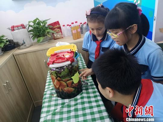 小学生们学习如何制作水果酵素。 张煜欢 摄