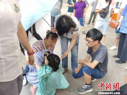 陈玉英(身着白衣者)询问发病女孩身体情况。桐乡卫校提供