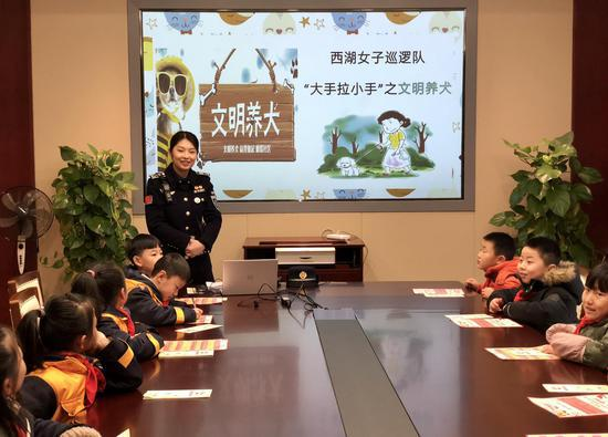 图为:队员贺萦文为孩子们讲解文明养犬知识。西湖景区执法局摄