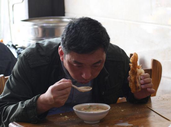 图为:一位顾客正在品尝咸豆浆。 王刚 摄