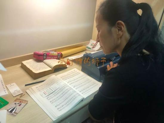 妈妈正在为女儿打盲文乐谱。张宇璐摄