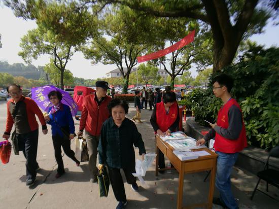 志愿者们向扫墓的群众发放塑料袋。王晨辉摄