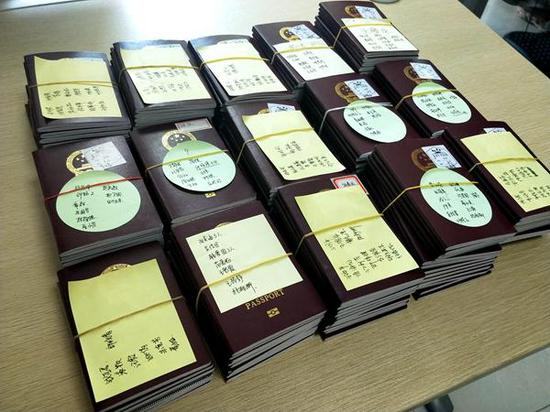 (5月16日,企业刚为员工们办好了护照。)