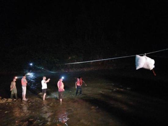 第二次救援,救援人员用绳索将物资运到对岸被困人员手中。