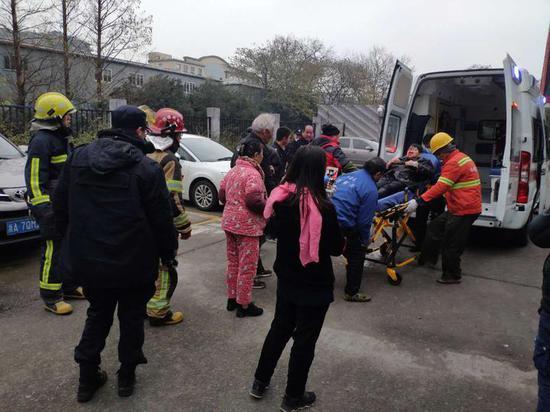 大家齐心救援,把大妈送上救护车。