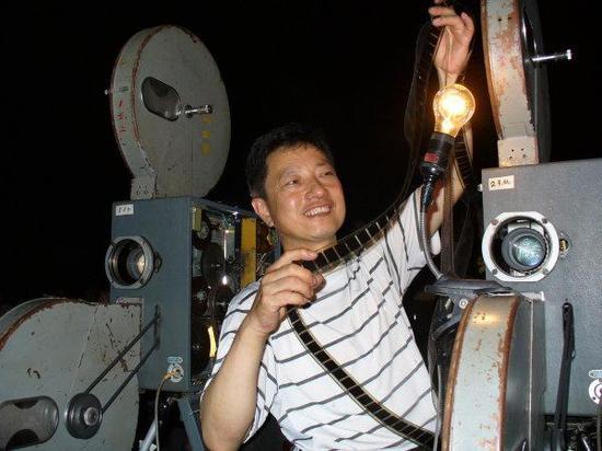 年轻时的杨志平在播映前查看电影胶片。