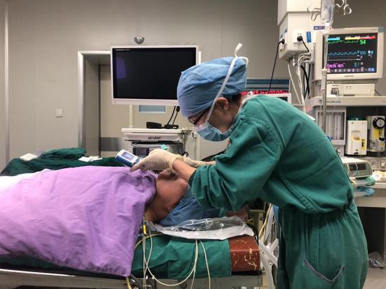 图为:医务人员正在为一位病人进行气管插管(非现场图) 叶倦 摄