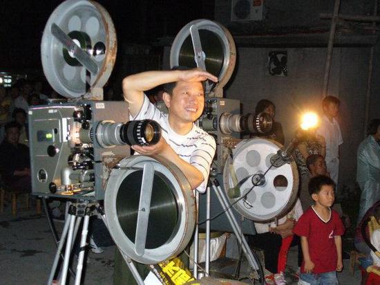 10多年前,杨志平操作35毫米电影放映机为大家服务。