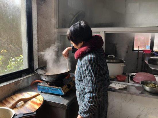 1月17日,东阳七秩塘村老年之家的厨师陈桃卿在为老人炒菜。