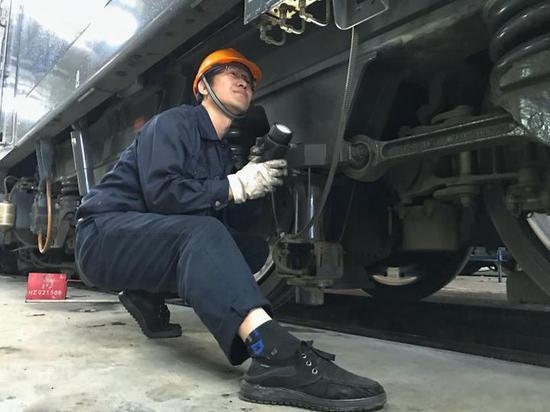 (中国铁路上海局集团有限公司杭州机务段检修工程师正在对春运代客机车走行部进行仔细检查,确保机车质量稳定可靠)