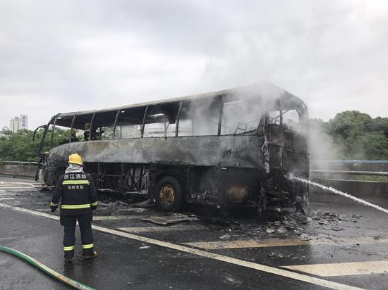 """大巴车被烧得只剩下""""铁架子"""" 金立 摄"""