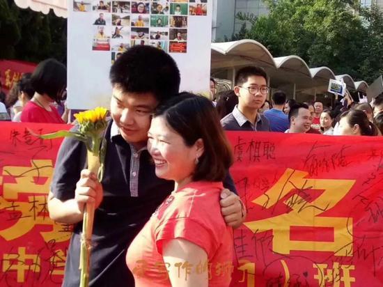 育才中学校长郜晏中,带着老师们站在门口。校长说:谢谢大家,祝孩子们成功!