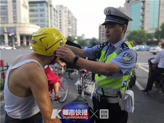 执勤交警教借头盔的市民如何正确佩戴头盔。