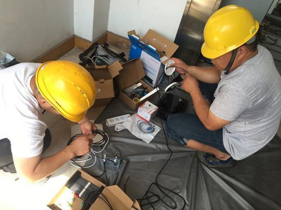 图为安装智慧电梯工作人员正在作业。越城区市场监管局供图
