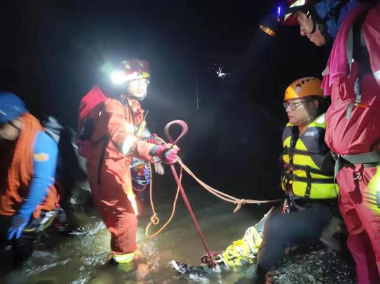 救援人员带着伤者穿过溪流。曾强 摄