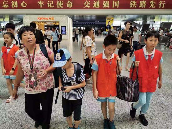 五年级小学生朱紫琪和曹宇歌帮旅客搬运行李