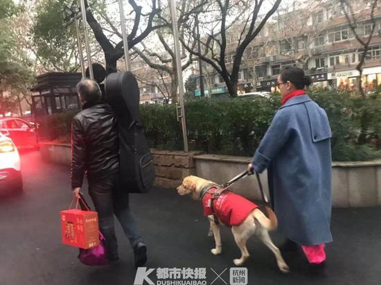 音乐会结束后,爸爸背着琵琶走在前面   阿拉丁带着小卉走在后面   摄影   刘永丽