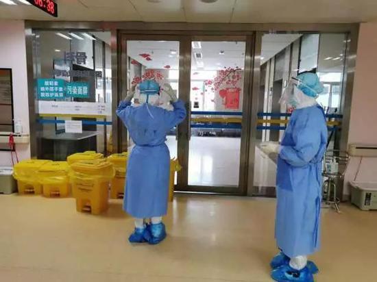 医护人员进入隔离病房,门口有院感班护士再次对其进行检查,确认无误后进入