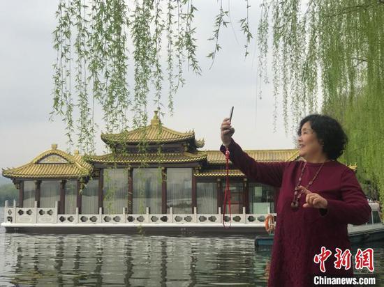 图为游客在拍摄西湖春景 江杨烨 摄