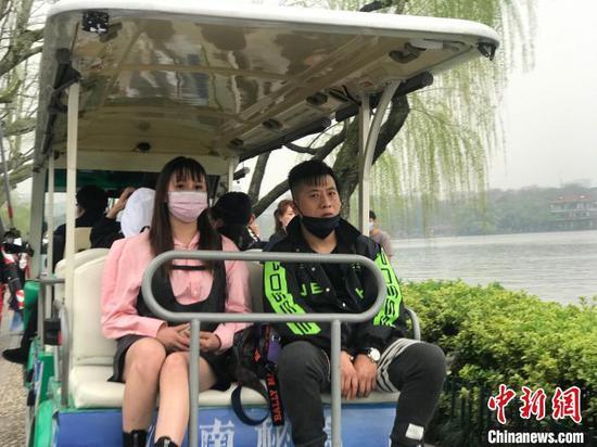图为部分游客乘坐观光车时已摘下口罩 江杨烨 摄