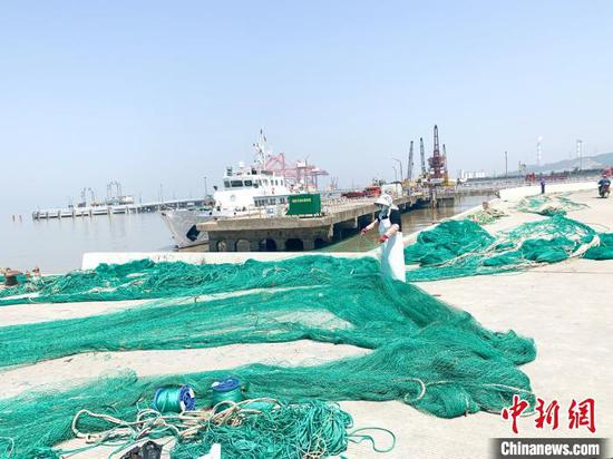 玉环市大麦屿鱼货码头,渔民正在修补渔网。 吕琼雅 摄