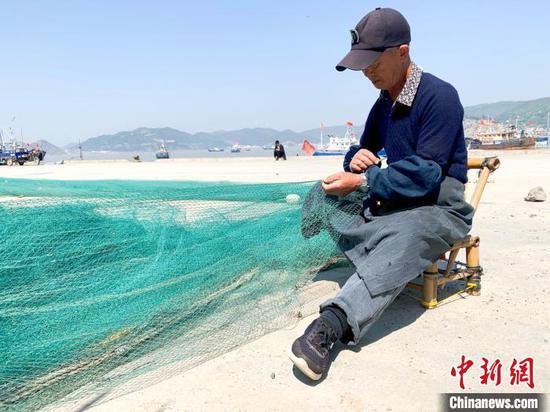 玉环市坎门中心渔港,渔民正在修补渔网。 吕琼雅 摄