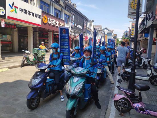 骑手团背着反诈旗帜宣传。杜恒达 摄
