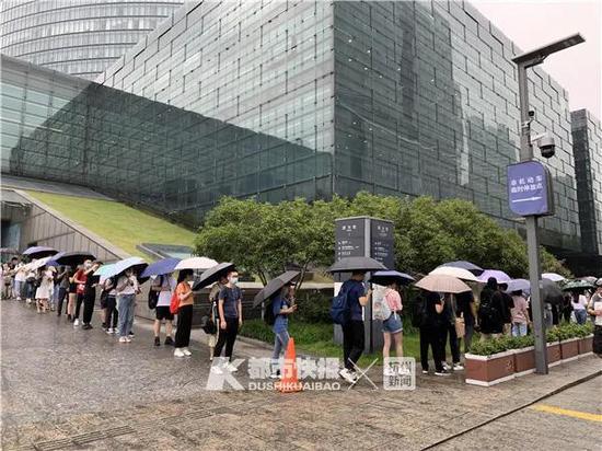 钱江新城杭州图书馆一座难求,一大早很多人冒雨排队。记者 潘卓盈 摄