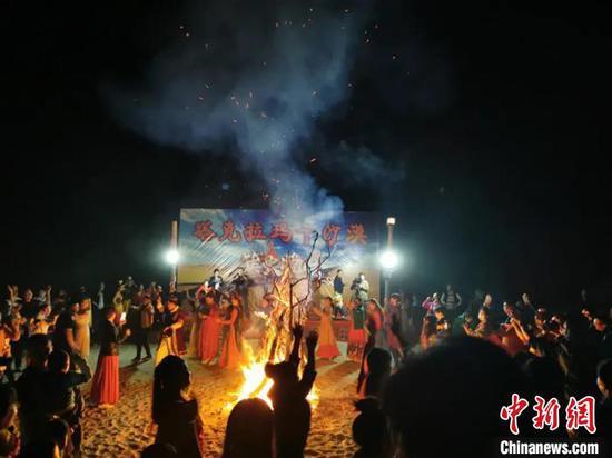 沙漠点燃篝火晚会,游客们载歌载舞,一片热闹景象。 赵丹丹 摄