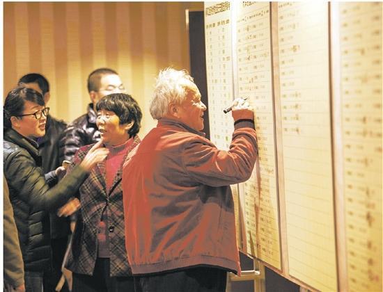 百姓在选房编号墙上,高兴地签下自己的名字