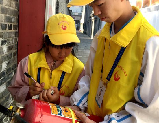 韦晓雨和盛泽韬正在检查和记录社区的灭火器。