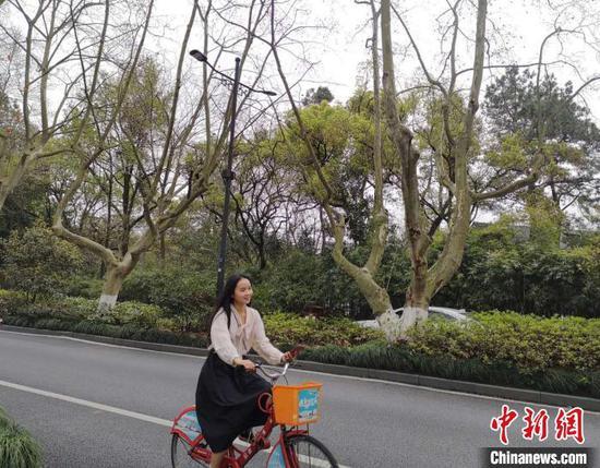图为游客骑车,已经摘下了口罩 童笑雨 摄