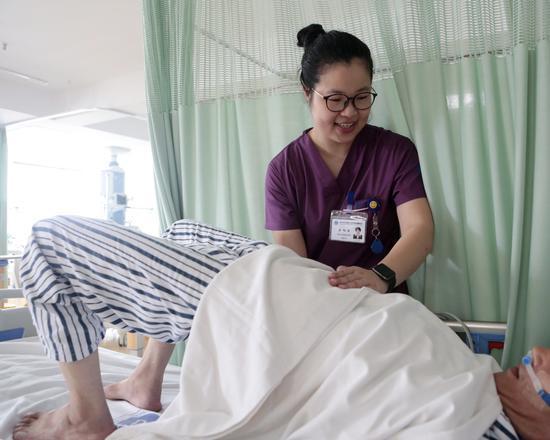 图为:吴旭佳正在照顾病人。 李婧 摄