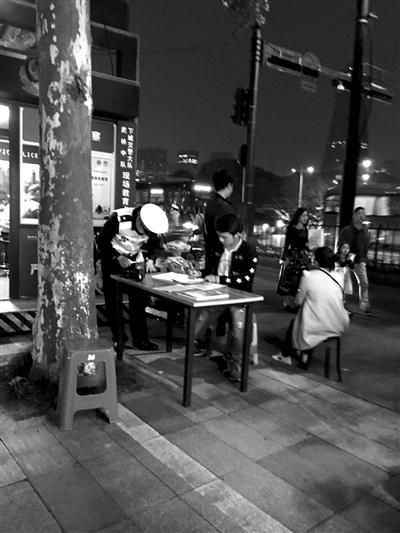 """昨晚7点40分,抄写交规的市民已挤不下中北桥岗4个""""受教位"""",交警安排一位市民到岗亭外的一张桌子上抄。 读者 曾先生 摄"""