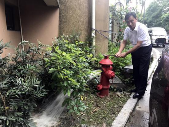 (宁沁家园物业负责人陈主任打开消火栓水阀门,水喷涌而出。)