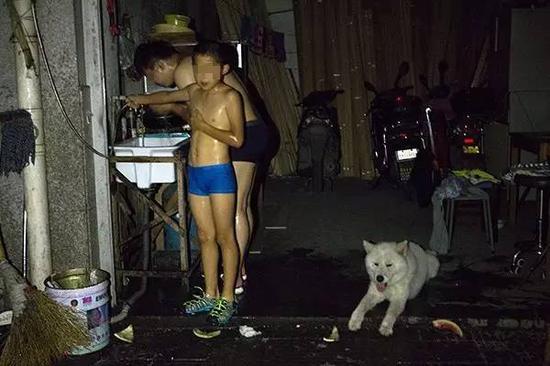 昨晚8点开始,银鼎商贸城部分住宅停电,一对父子在黑暗中淋浴。记者 葛亚琪 摄