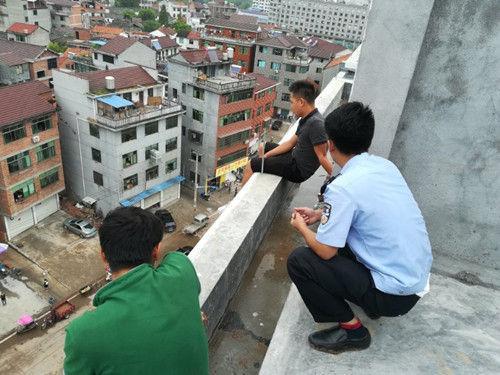 图为:民警对欲跳楼的男子进行劝导。傅村派出所供图