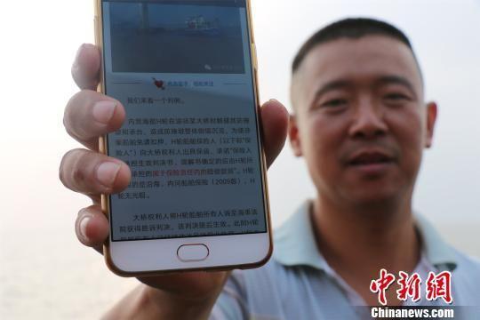 图为:渔民在微信里了解海上避碰规则。 何蒋勇 摄