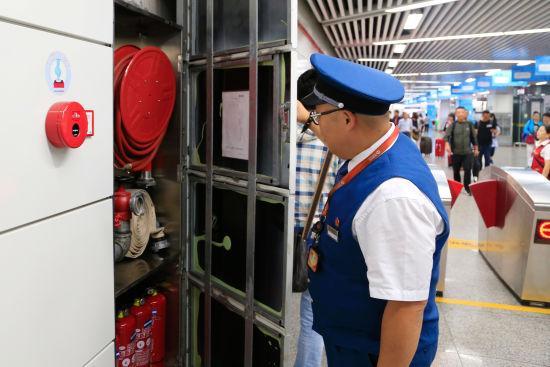 图为:值班站长正在检查地铁站消防设施的安放情况。 王远 摄