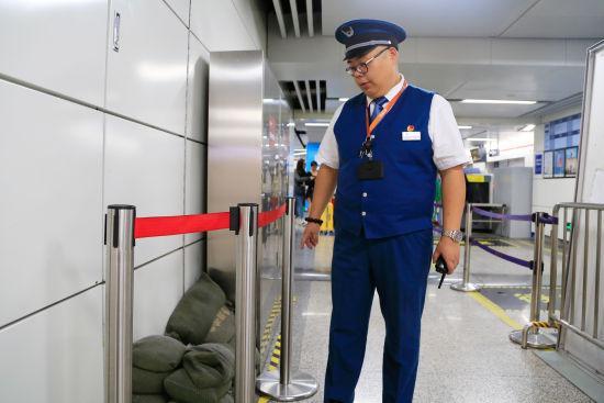 图为:值班站长正在检查地铁站防汛物资的摆放。 王远 摄