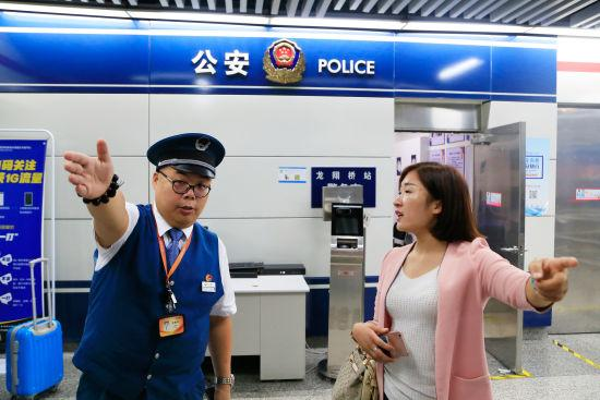 图为:值班站长正在给一名乘客指路。 王远 摄