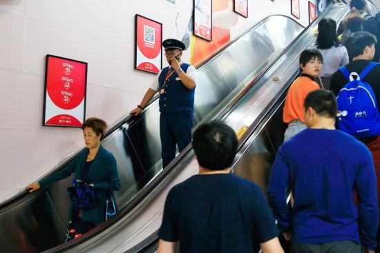 图为:值班站长正在巡查地铁站出入口情况。 王远 摄