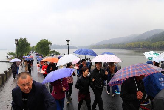 众多游客正在西湖断桥上游览。 王远 摄
