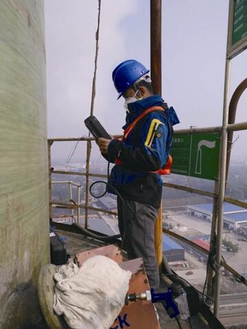 陈禾逸在山东爬上78米高的烟囱平台监测废气