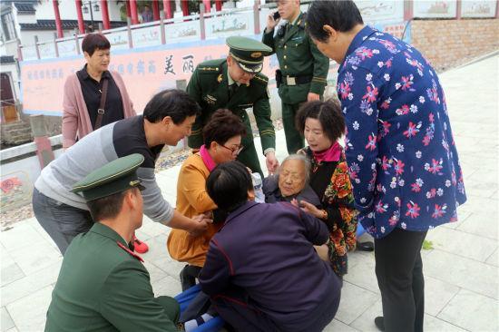 图为:边防官兵安慰受伤老人。 邹训永 摄
