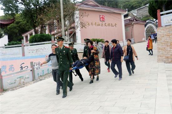 图为:边防官兵与群众一起将受伤老人抬往医院治疗。 邹训永 摄